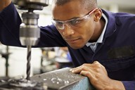 Close Up Of Apprentice Engineer Using Milling Machine